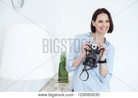 Attractive young woman is photographing her home. She is standing and holding a retro camera. The lady is smiling with happiness