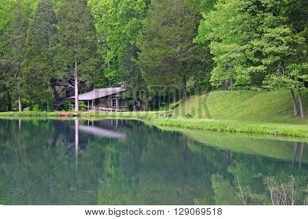 a country cabin is reflected in the calm waters of a lake