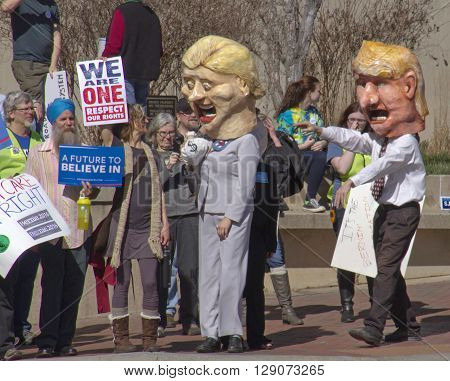 Asheville, North Carolina, USA - February 28, 2016: Parody of Donald Trump trying to catch up to Hillary Clinton's as she holds onto a bag of money as skeptical Bernie Sanders supporters holding signs watch at a Bernie Sanders campaign rally on February 2