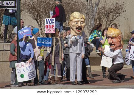 Asheville North Carolina USA - February 28 2016: Humorous effigies of Donald Trump kneeling at Hillary Clinton's feet as she holds onto a bag of money while skeptical Bernie Sanders supporters holding signs watch at a Bernie Sanders campaign rally on Febr