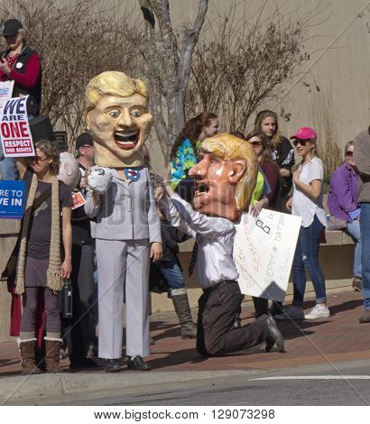 Asheville,North Carolina, USA - February 28, 2016: Humorous effigies of Donald Trump kneeling at Hillary Clinton's feet as she holds onto a bag of money while skeptical Bernie Sanders supporters holding signs watch at a Bernie Sanders campaign rally