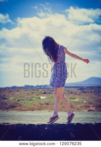 Young woman traveler weared dress in desert. Colored photo