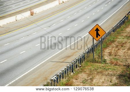 merge sign by the side of multi-lane highway