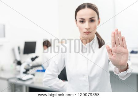 Stop disease. Cheerful female scientist is stretching arm toward the camera. She is standing and looking forward with seriousness. Her colleague is sitting on background