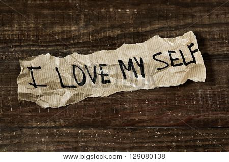 the text I love myself written in a piece of paper, placed on a rustic wooden surface