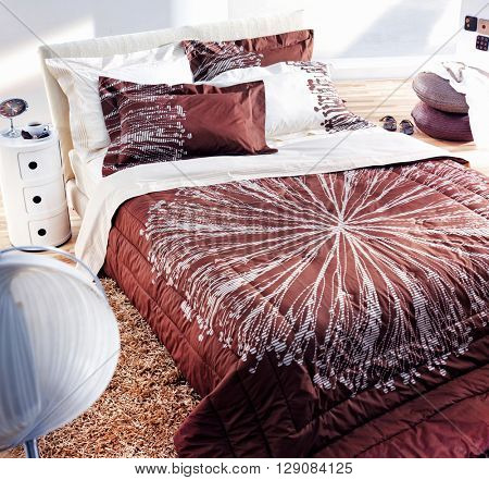 MODERN BEDROOM, INTERIOR , WHITE AND BROWN COVERS WITH ABSTRACT PATTERN AND MINIMAL  DECORATION WITH ETHNIC ELEMENTS