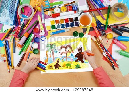 animals on beach sand and sea child drawing, top view hands with pencil painting picture on paper, artwork workplace