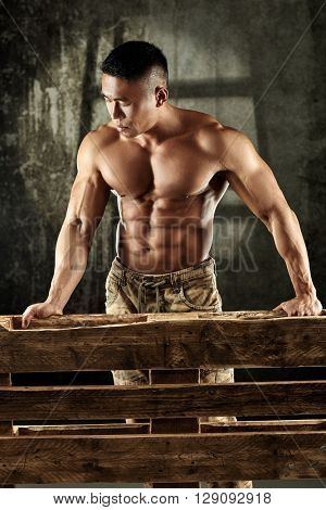 Muscular asian man standing behind pallet, looking down.