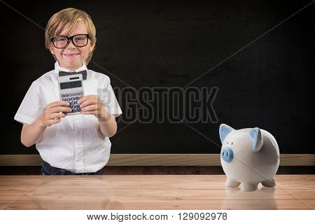 Cute pupil using calculator against blackboard on wall