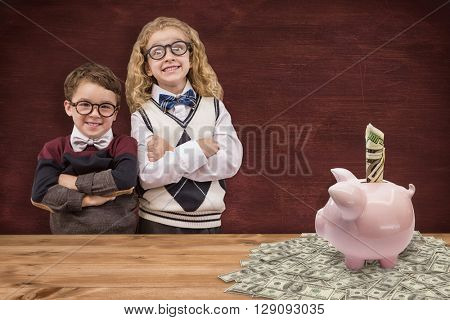 Cute pupils looking at camera against image of a desk