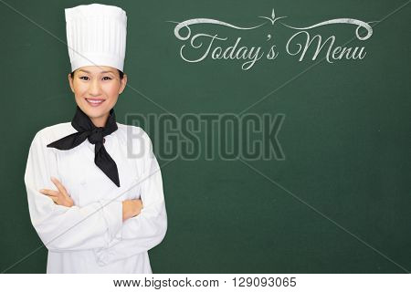 Composite image of woman chef smiling against a blackboard