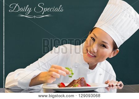 Daily specials message against smiling female chef garnishing food in kitchen