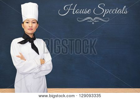 Portrait of confident female cook in kitchen against house specials message
