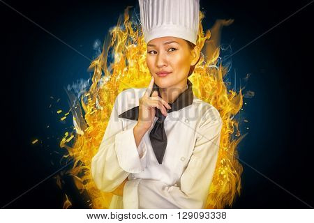 Portrait of thoughtful female cook in kitchen against blue background with vignette