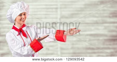 Pretty chef presenting with hands against digitally generated grey wooden planks