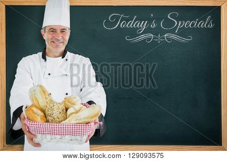 Composite image of chef smiling and holding a bread basket against a blackboard