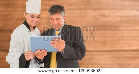 Businessman and female chef using digital tablet against overhead of wooden planks