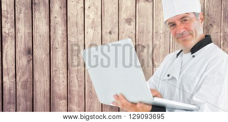 Composite image of friendly chef holding a laptop against a wooden background