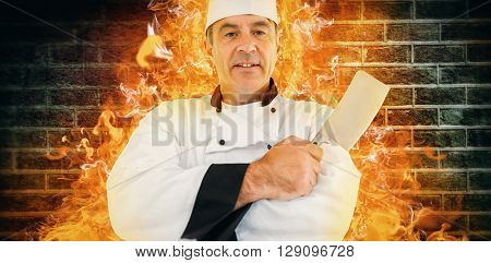 Portrait of a serious chef holding a knife against image of a wall
