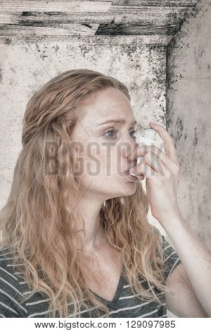 Woman using the asthma inhaler against image of a room corner