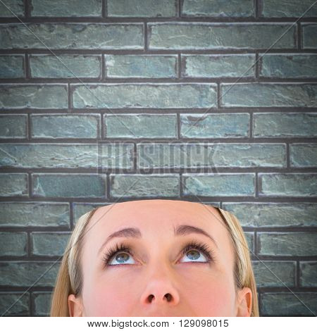 Close up of blonde woman looking up against a stone wall