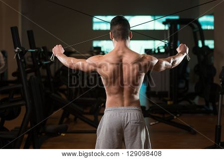 Bodybuilder Exercising Shoulders On Cable Machine