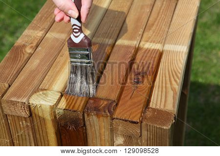 Woman painting wooden furniture piece