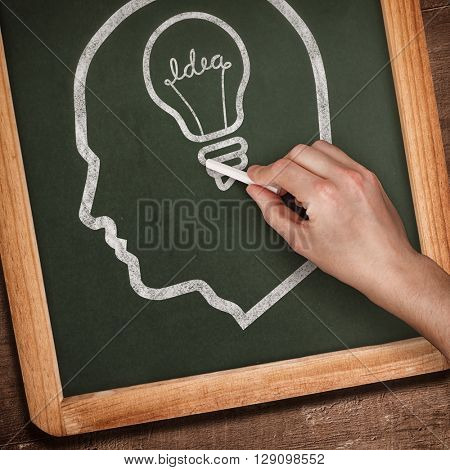 Hand writing with chalk against chalkboard
