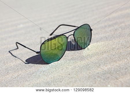 Sunglasses on the sand , reflection of beach in sunglasses