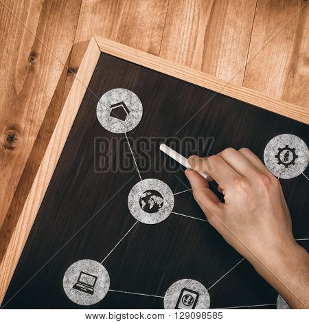 Hand writing with chalk against small blackboard on wooden floor