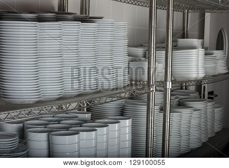 stacks of many white plates on a wire rack shelf in a commercial kitchen