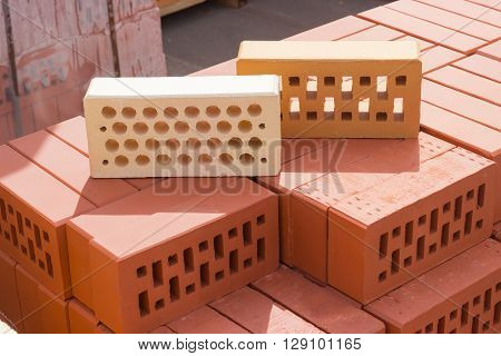 Two common perforated bricks of different colors with round and rectangular holes on a pallet with bricks on the background other pallets with bricks