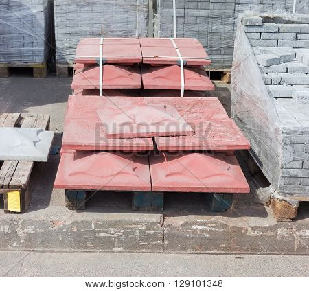 Red concrete decorative relief tiles for landscaping made by vibration casting method stacked on a pallet on a warehouse