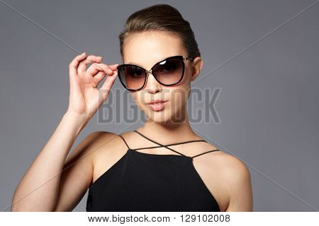 accessories, eyewear, fashion, people and luxury concept - beautiful young woman in elegant black sunglasses over gray background