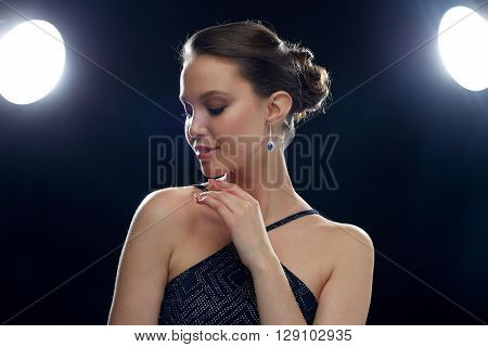 beauty, jewelry, people and luxury concept - beautiful young asian woman with earring over black background and spotlights