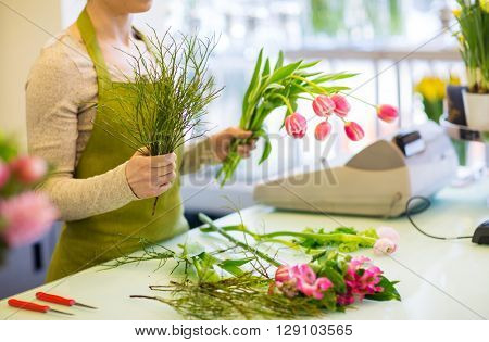 people, business, sale and floristry concept - close up of florist woman making tulip bunch at flower shop