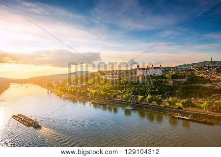 Bratislava aerial cityscape view on the old town with, castle hill Danube river and cargo ship on the sunset in Slovakia