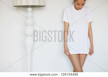 Close Up Shot Of Young Female Model Posing Against Home Interior, Wearing White Blank Loose Copy Spa