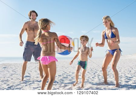 Happy family playing with ball at beach. Daughter playing with her brother and parents at beach. Family having fun together in a summer holiday.