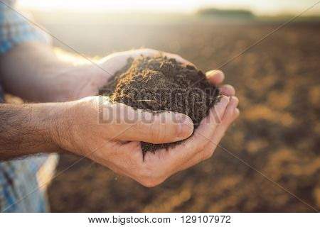 Handful of arable soil in hands of responsible farmer close up selective focus