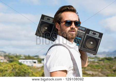 Portrait of a handsome young man holding radio near ears. Close up of hipster guy listening to music on a summer day. Man wearing sunglasses and holding on his shoulder a vintage radio.
