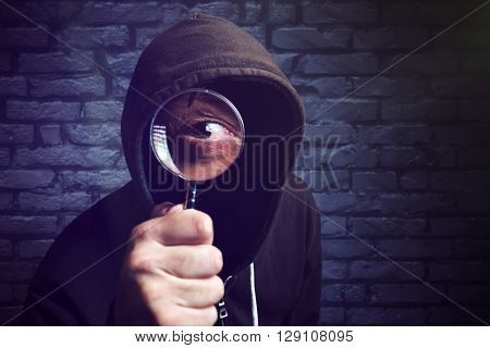 Hooded computer hacker with magnifying glass internet hacker and online security concept.