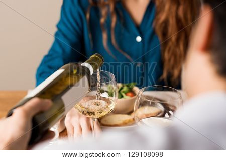 Rear view of a man serving white wine in a glass. Young couple enjoying meal and drinks at home. Close up of man hand pouring wine at his girlfriend.
