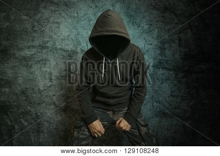 Spooky evil criminal person with hooded jacket in front of concrete wall.