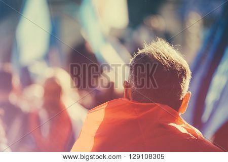 Unrecognizable older adult person on outdoor political meeting from behind looking toward gathered crowd and stage. poster