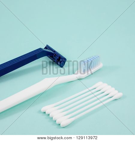 The purified white cotton buds with white toothbrush and dark blue plastic razor.