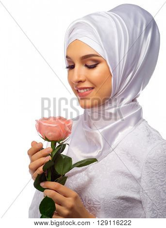 Young muslim woman with rose flower isolated