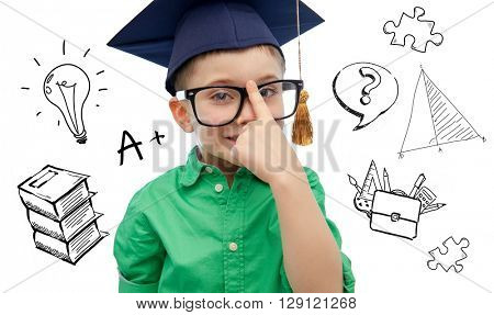 childhood, school, education, knowledge and people concept - happy boy in bachelor hat or mortarboard and eyeglasses over doodles