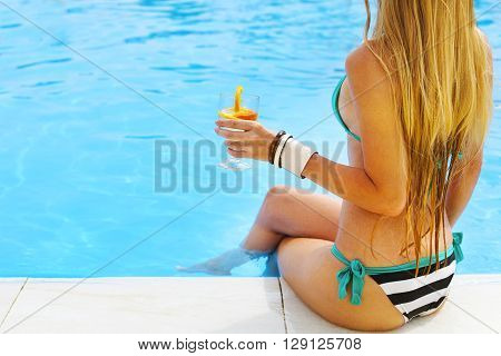 Pretty blond woman enjoying cocktail near the swimming pool. Close up
