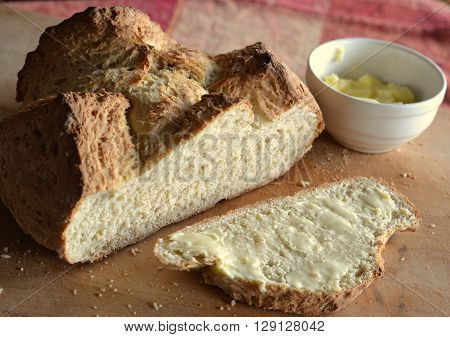 Irish Soda Bread - loaf sliced and bread slice is buttered. Small dish of butter is visible.
